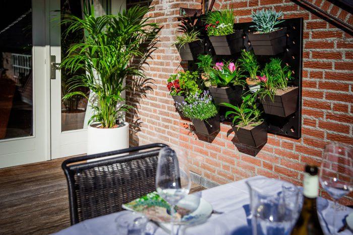 Verticale tuin met bloembakken en bloempotten buiten