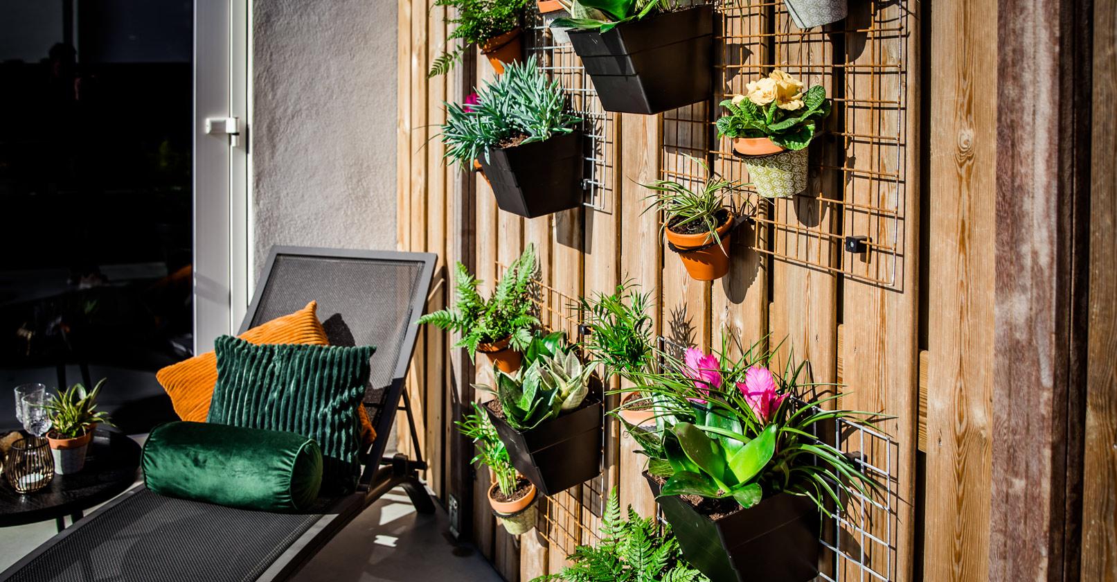 Verticale tuin roosters met bloempotten en bloembakken aan schutting